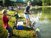 An unidentified man helps land a fish during the annual Kids Fish Day at Town Bluff/BA Steinhagen Lake on May 12, 2012.