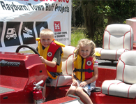 Unidentified children enjoy a boat on land during a water safety event at Town Bluff/BA Steinhagen Lake on May 12, 2012.